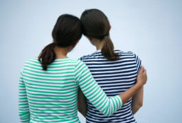 Two women seen from behind with arms around each other.