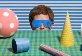 Humorous photograph shows a young man with plastic sunglasses on that match the patterns around him, surveys a tabletop scene of patterned objects.