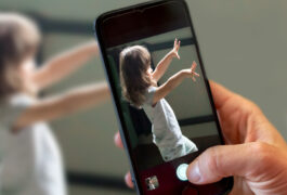 Close up of phone with Cognoa app in use, apparently taking video or a photo of a child exhibiting stimming behaviors or repetitive motions.
