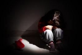 Sad child sitting in the dark