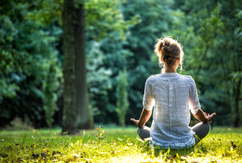 Woman doing yoga on grass field