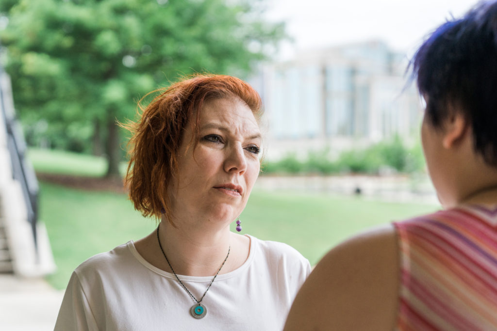 Johanna Verburg looks concerned while talking to another person.