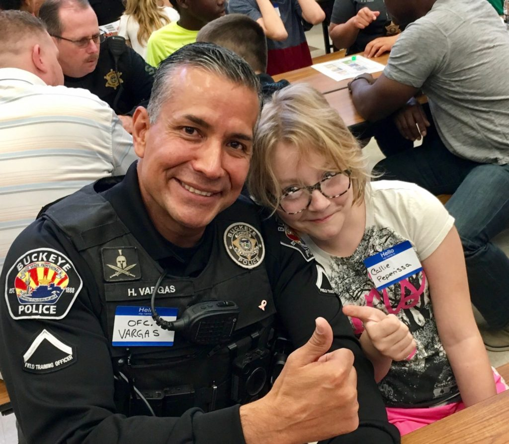 A smiling police officer poses with a child, also smiling.