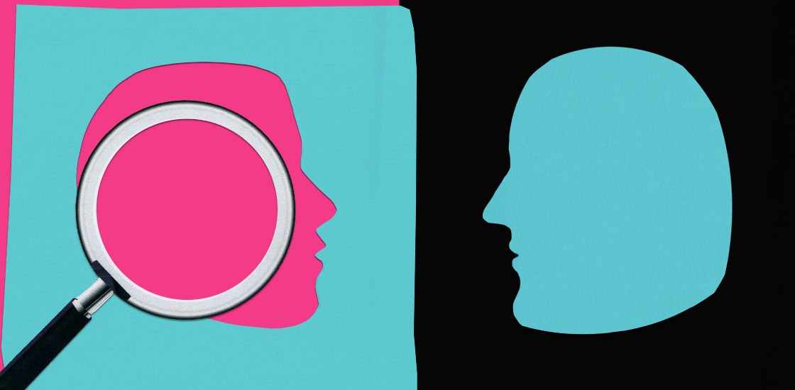 Female head shape cut out of pink paper, under magnifying glass. Male head is in blue, opposite the female.