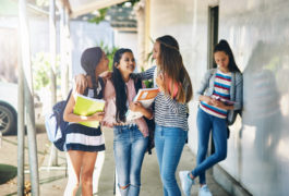 three teenage girls talking and laughing in school hallway while one girl stands alone to the side.