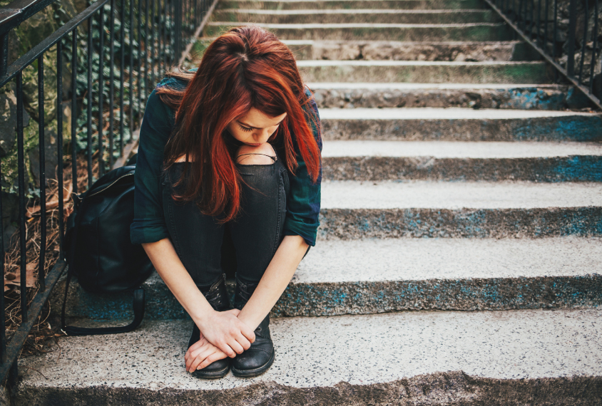 Teen girl sits on stairs, alone, downcast.