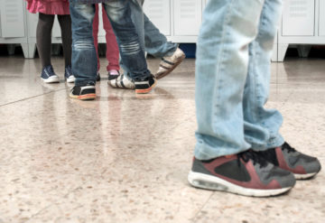 Kids shoes in hallway showing one boy standing alone by a group.