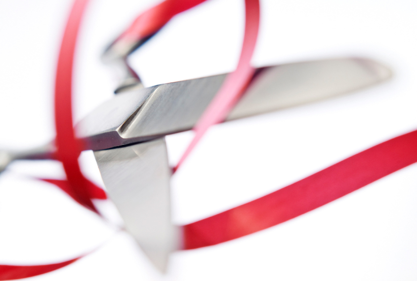 silver scissors float on white, about to cut a red ribbon.