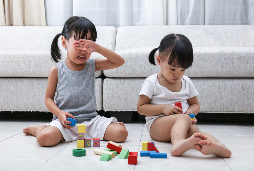 Two female children playing with blocks, one is crying, the other is facing away.