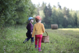 Two children picking mushrooms in a field.