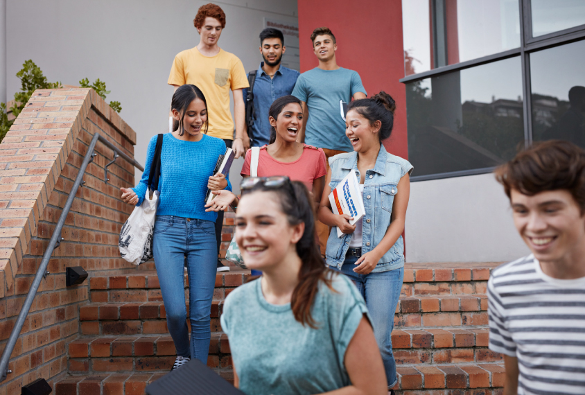 A group of high school kids walking down a set of stairs outside a building.
