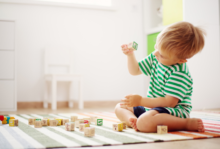 A young boy plays with blocks