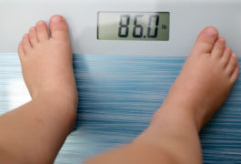 Feet of a child on a scale, weighing in at 86 pounds.