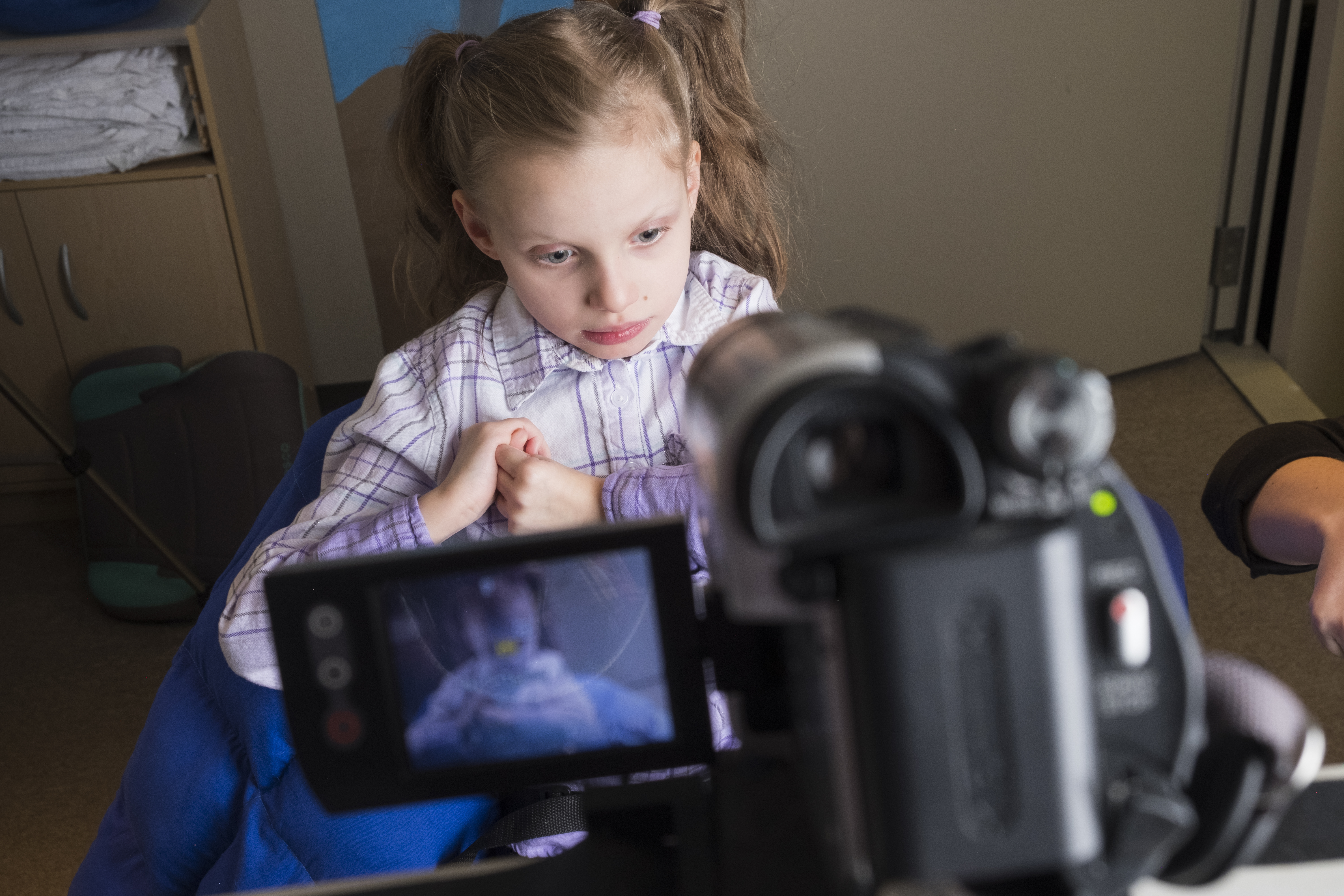 Image shows a young girl sitting in front of a camera.
