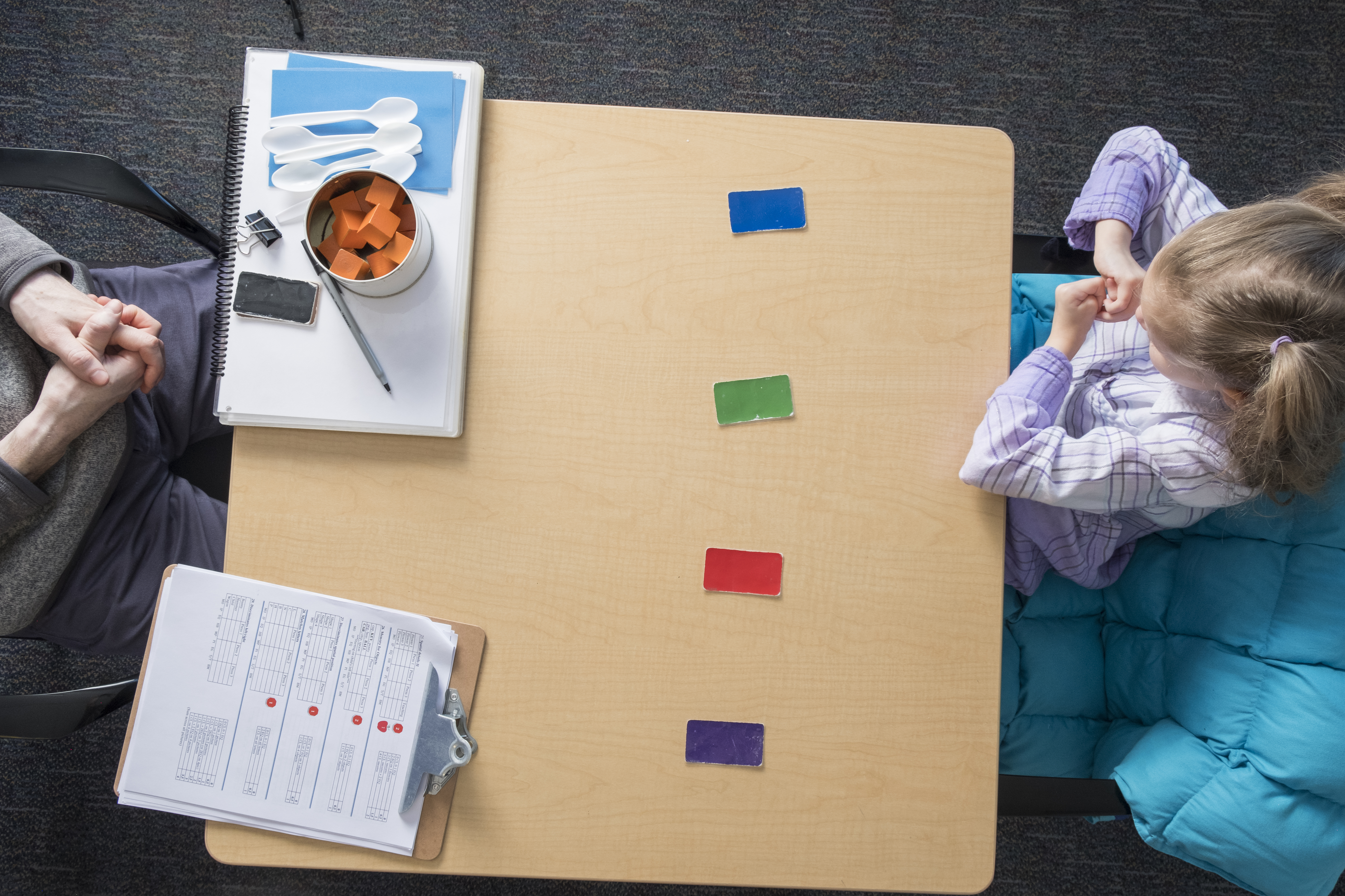 Image shows an overhead view of a young child sitting at a table with a researcher.