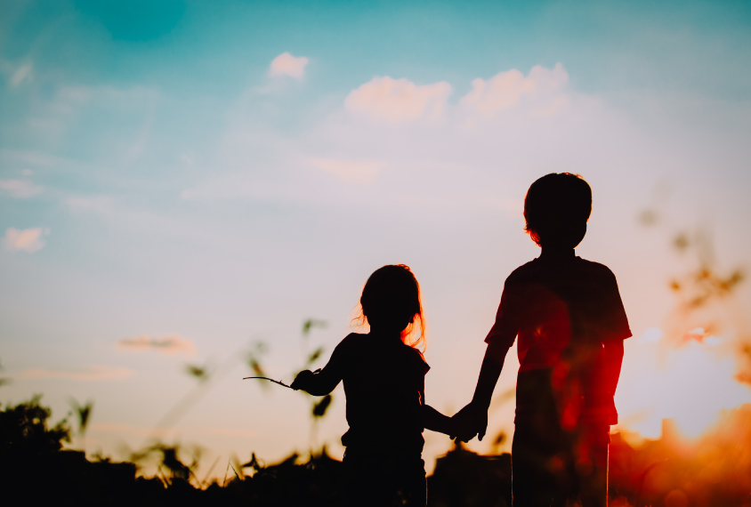 Two young siblings holding hands.
