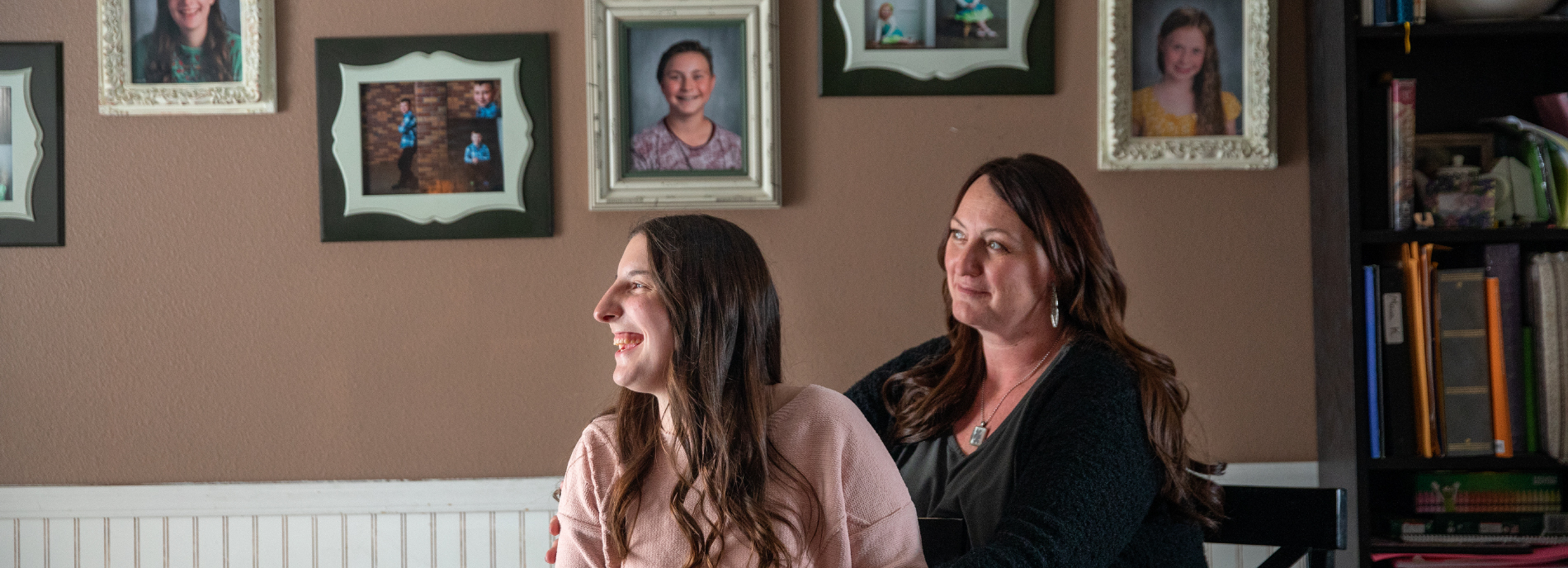 Mother and daughter look to their right. Photos are in the background, along with a wall clock.