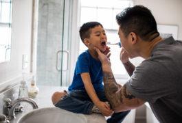 Father helping boy brush teeth