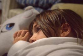 Child awake in bed at night