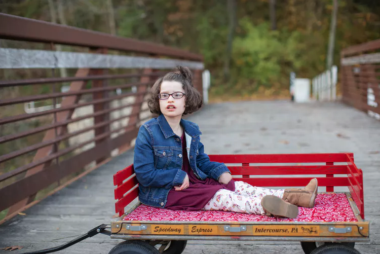 Child with Pitt-Hopkins syndrome seated in a red wagon outside.