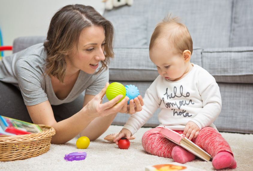 Mother offers toys to toddler