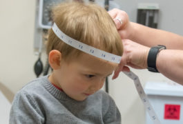 Toddler having head measured at clinic