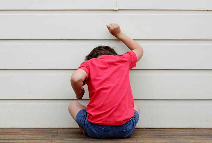 a boy in red knocking on a wall