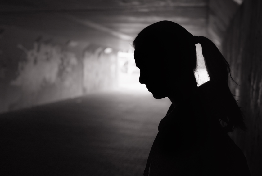 A depressed young woman in a tunnel