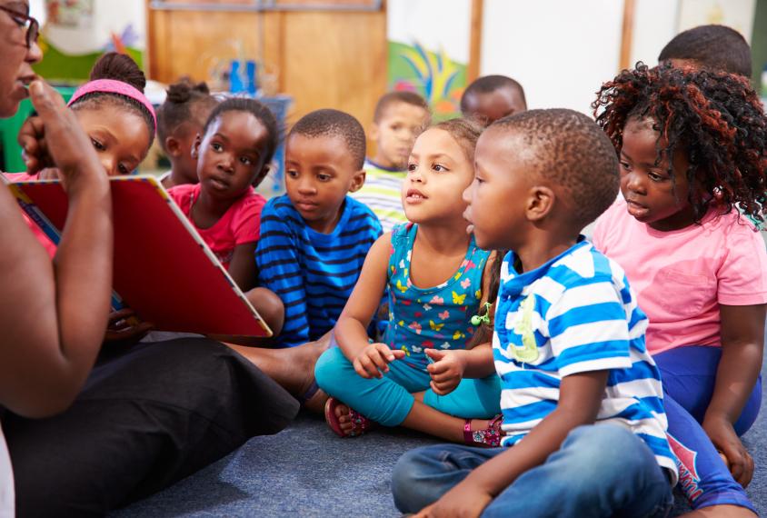 Teacher reading a book with a class of children
