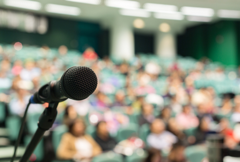 auditorium conference scene with microphone in foreground.