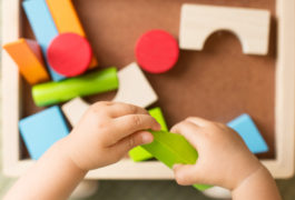 Toddler's hands playing with educational toys