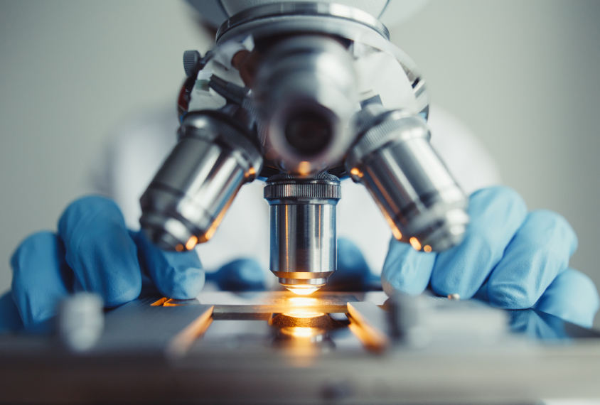 close up of microscope and researcher's gloved hands