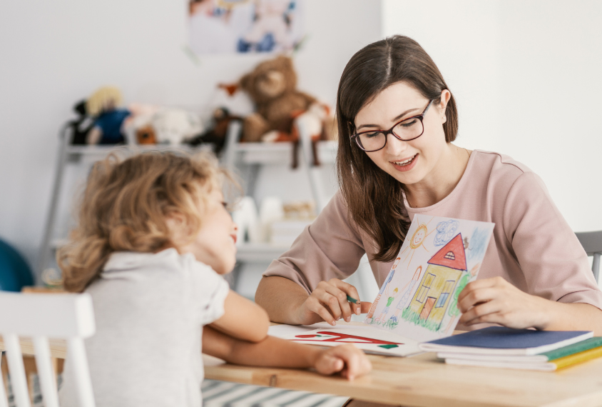 therapist in session with child, showing picture cards.
