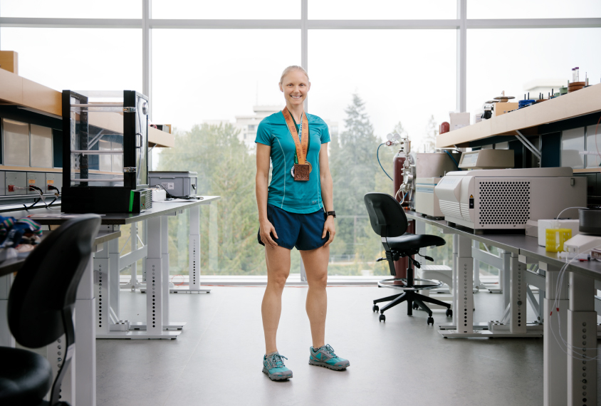 Scientist Annie Ciernia standing in her lab, wearing her running gear and medals.