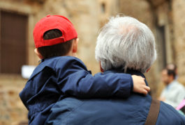 Older father carries son in reed baseball cap