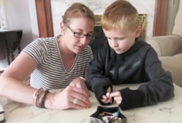 Mother and son play with small toys on tabletop