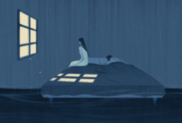 Woman on bed sits alone while man sleeps in bed behind her