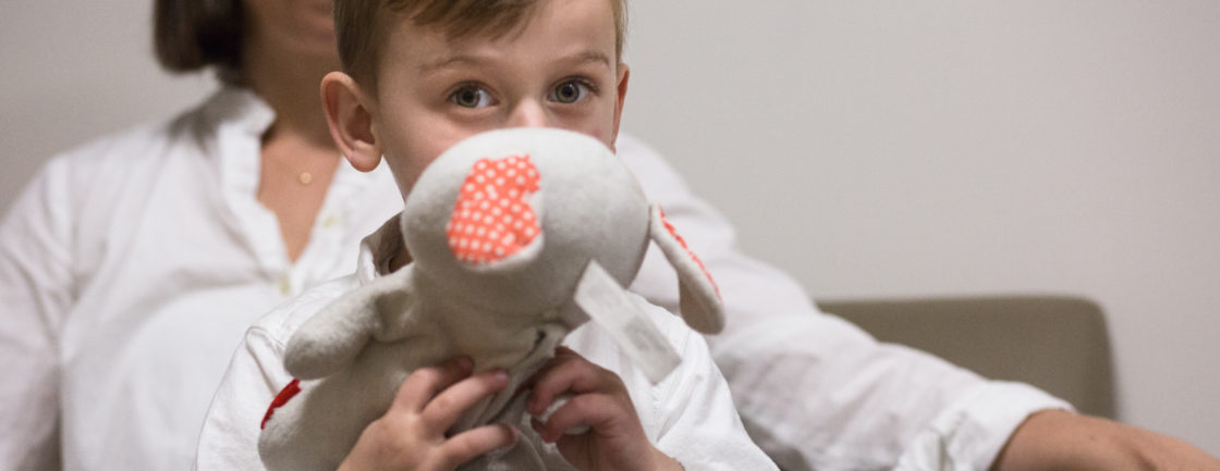 Photo: A young child, named Owen, in the waiting and resting area during his testing at the Yale Child Study Center. He clutches a stuffed toy bunny.