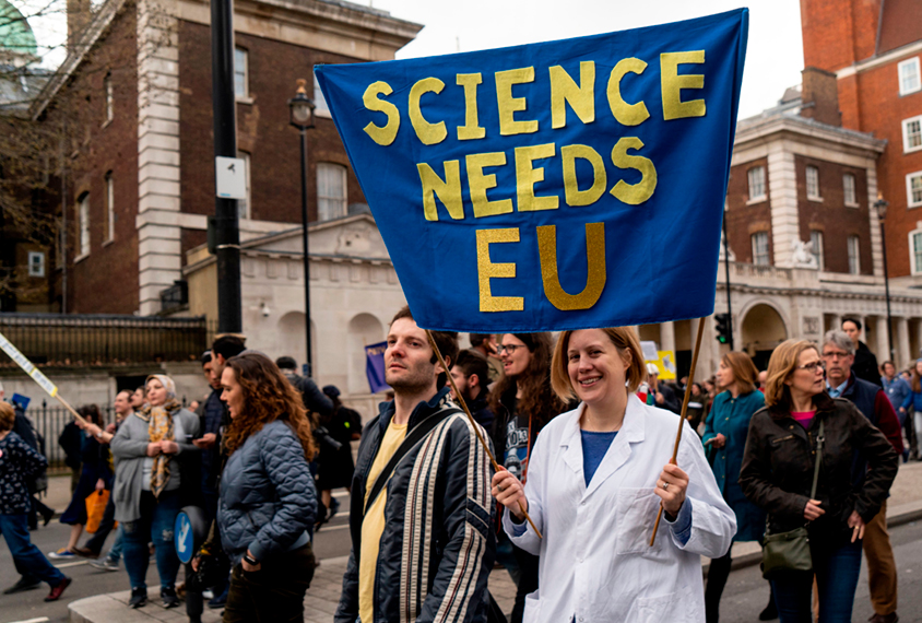A scientist protesting Brexit holds a 'Science needs EU' banner on a march in London