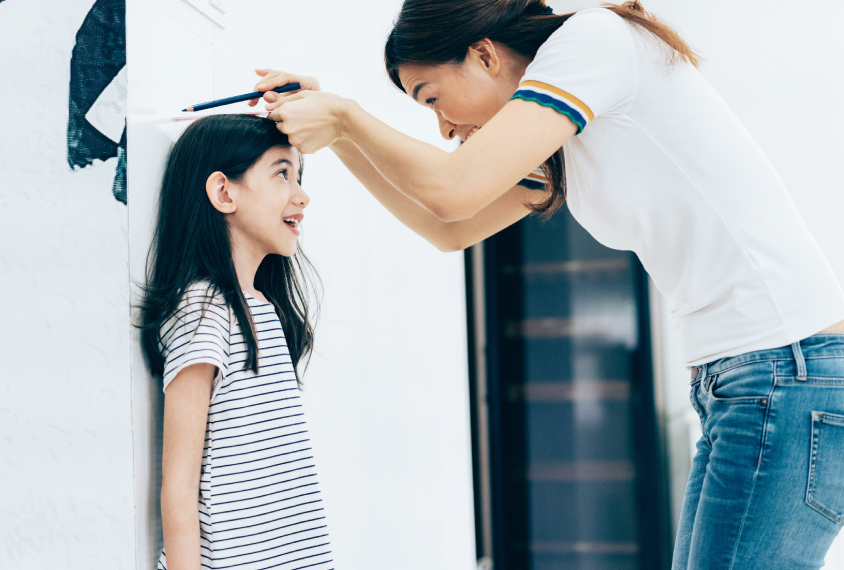 a young girl has her height measured by a woman