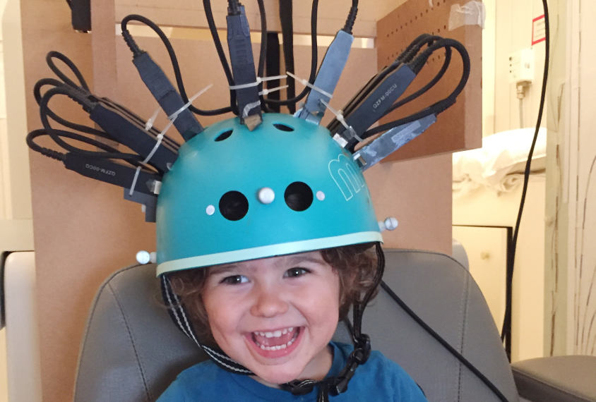 Child in a bike helmet repurposed as a brain scanner, smiles and laughs