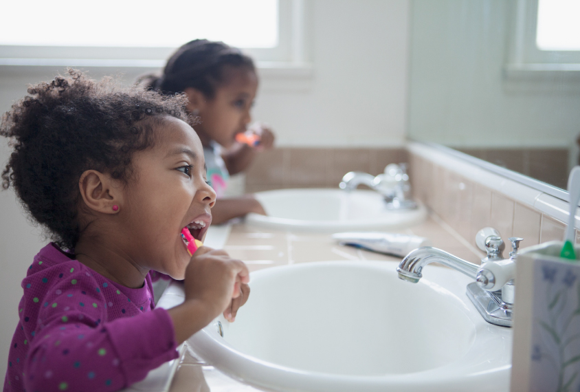 Two children brush teeth in bathroom