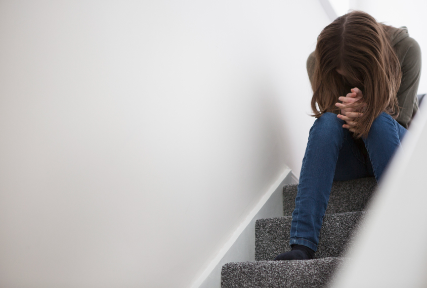 A young teen woman sits on stairs with her head hanging down, her face hidden by her hair.
