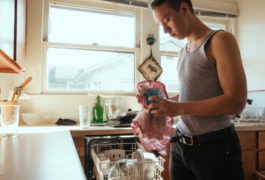 Young man drying dishes in kitchen