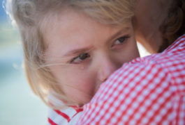 Young girl crying into mother's shoulder