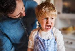 Toddler cries, looking away from parent