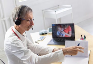 doctor with remote patients on screen in his office