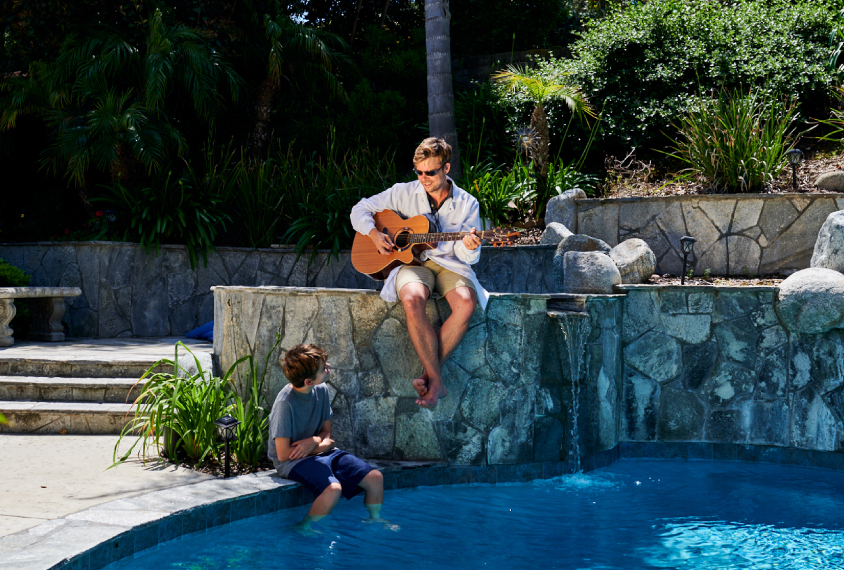 Dr. Jack Gilbert with one of his kids in his backyard, playing guitar