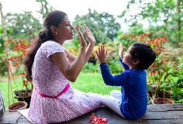 Mother and child play game using hands