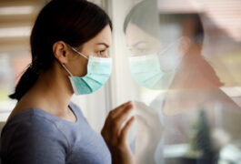 A young woman wearing a face mask looks out the window
